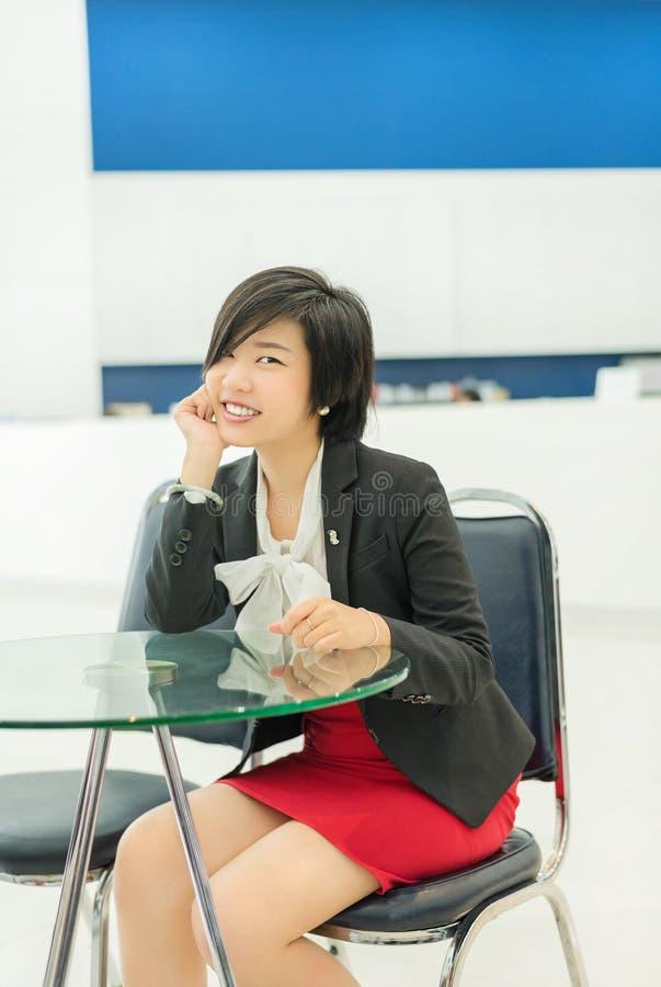 Empresaria (asiática) tailandesa linda que se sienta y que sonríe en la oficina foto de archivo