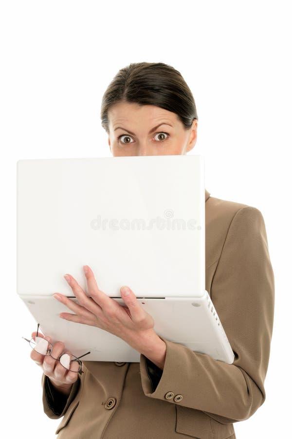 Empresaria asustada que usa la computadora portátil imagen de archivo libre de regalías