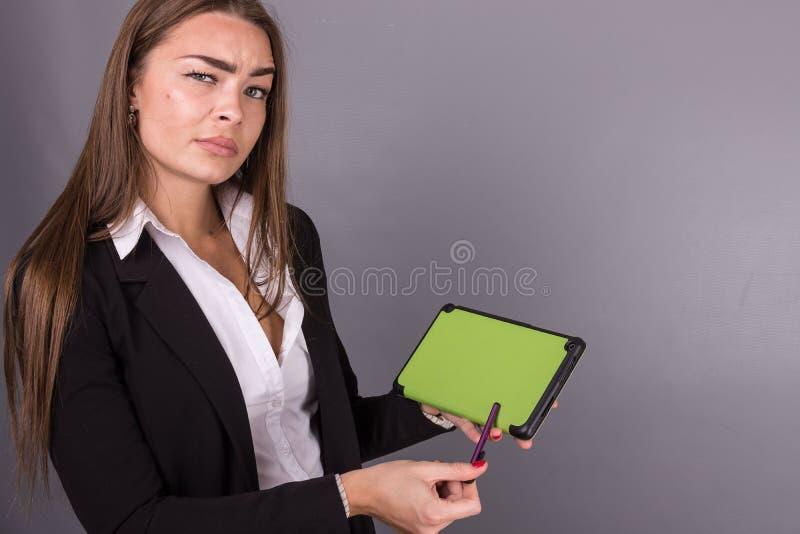 Empresaria atractiva con la tableta que estudia noticias e ideas de la presentación foto de archivo libre de regalías
