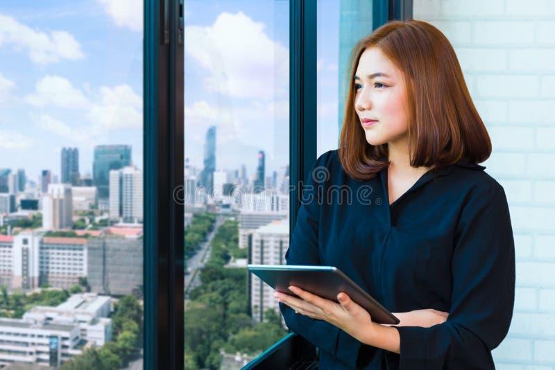 Empresaria atractiva del yound que sostiene la tableta del ordenador y profundamente fotografía de archivo libre de regalías