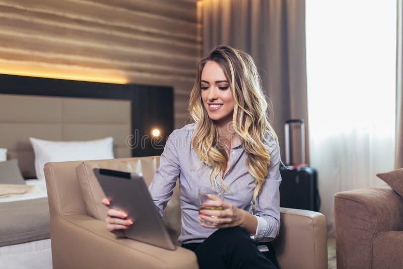 Empresaria atractiva en la habitación usando la tableta digital imagen de archivo libre de regalías