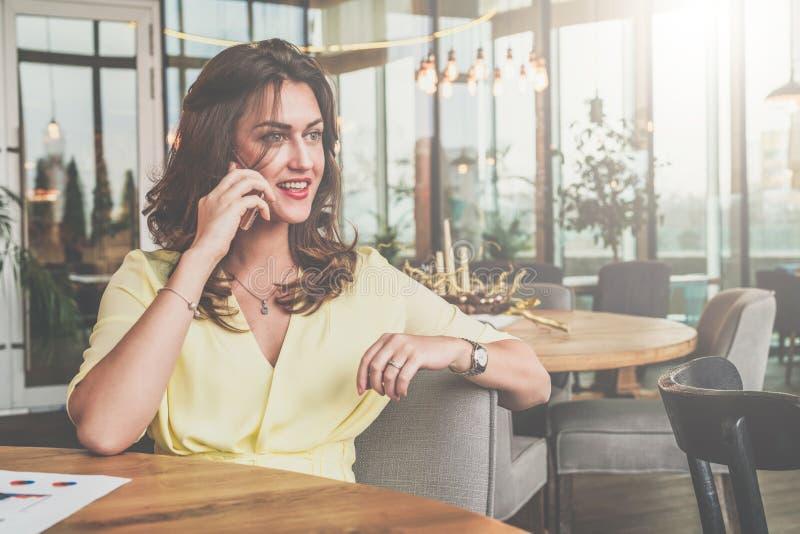 Empresaria atractiva joven que se sienta solamente en la tabla en café y que llama por el teléfono móvil foto de archivo