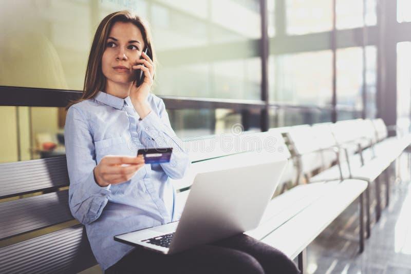 Empresaria atractiva joven que sostiene la tarjeta de crédito en mano femenina y que usa smartphone y el ordenador portátil móvil fotos de archivo