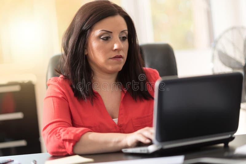 Empresaria atractiva joven que trabaja en el ordenador portátil, efecto luminoso foto de archivo libre de regalías