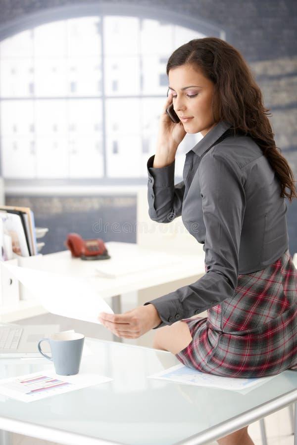 Empresaria atractiva que charla en el teléfono en oficina imágenes de archivo libres de regalías