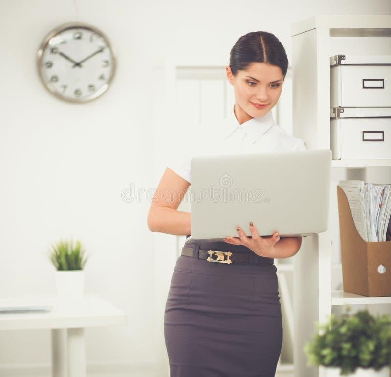 Empresaria atractiva que se coloca en oficina con el ordenador portátil fotografía de archivo libre de regalías
