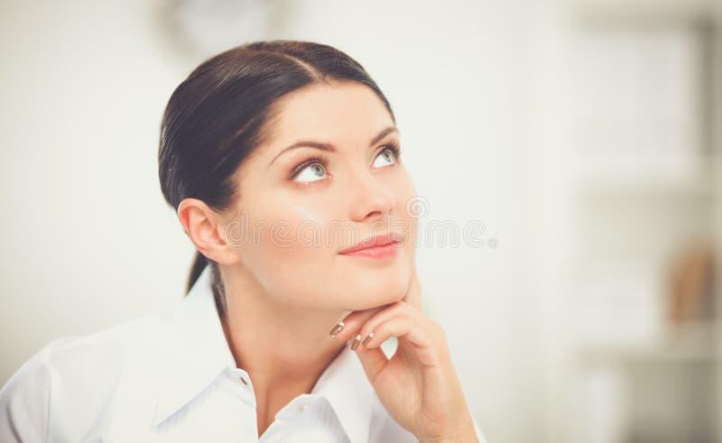 Empresaria atractiva que se sienta en el escritorio en la oficina imágenes de archivo libres de regalías