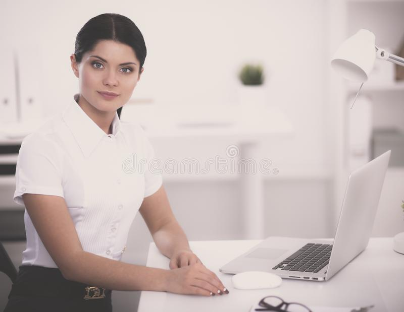 Empresaria atractiva que se sienta en el escritorio en la oficina fotografía de archivo