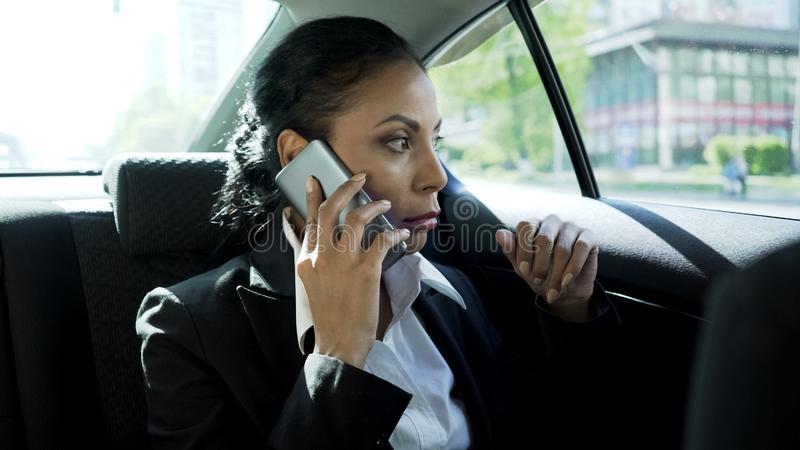 Empresaria atractiva que se sienta en el taxi, hablando en el teléfono, conversación seria imágenes de archivo libres de regalías