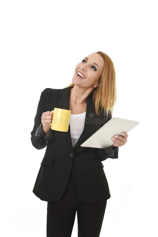 Empresaria atractiva que sostiene thoughtfu de mirada feliz sonriente del traje de negocios del cojín digital de la tableta que l foto de archivo