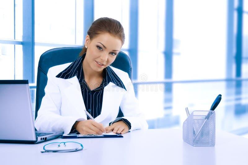 Empresaria atractiva que trabaja con el ordenador portátil en la oficina imagen de archivo libre de regalías
