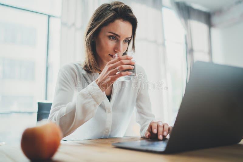 Empresaria atractiva que trabaja en el ordenador port?til en su lugar de trabajo en la oficina moderna Fondo enmascarado imagenes de archivo