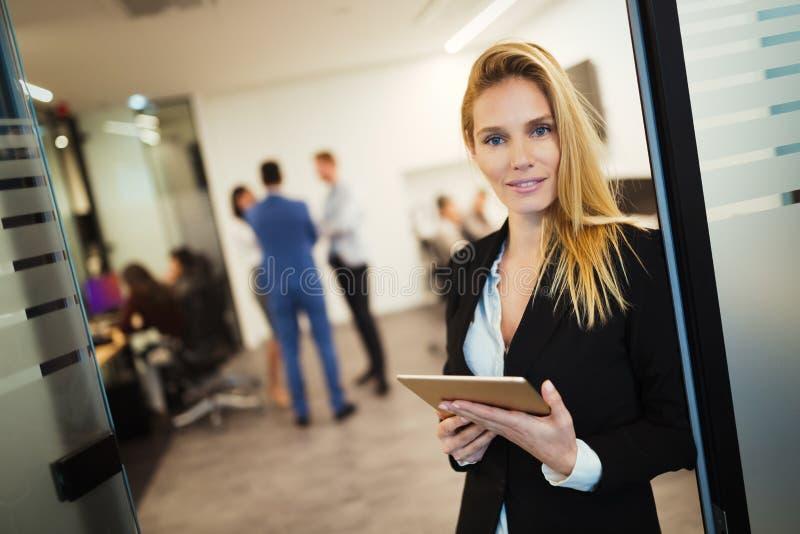Empresaria atractiva que usa la tableta digital en oficina fotografía de archivo
