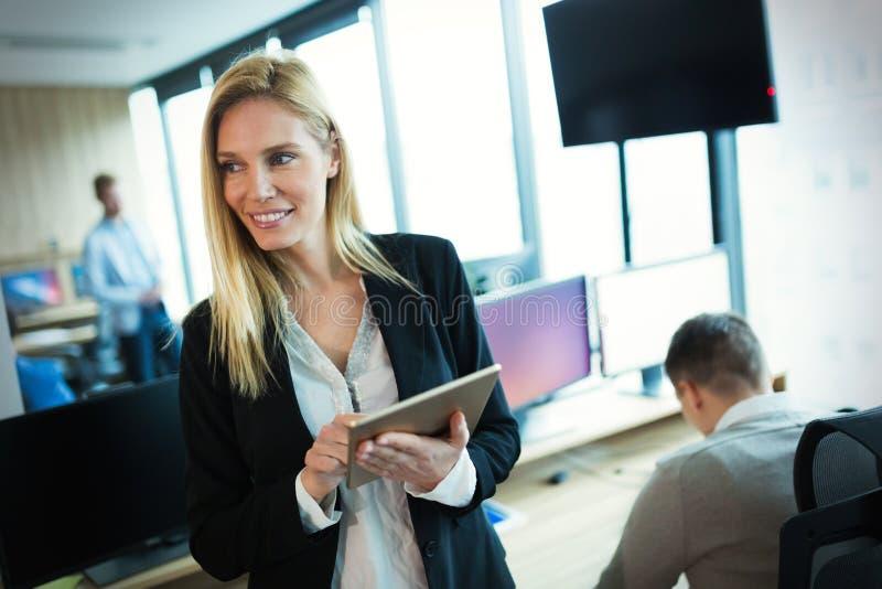 Empresaria atractiva que usa la tableta digital en oficina fotografía de archivo libre de regalías