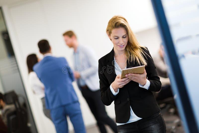 Empresaria atractiva que usa la tableta digital en oficina imagen de archivo libre de regalías