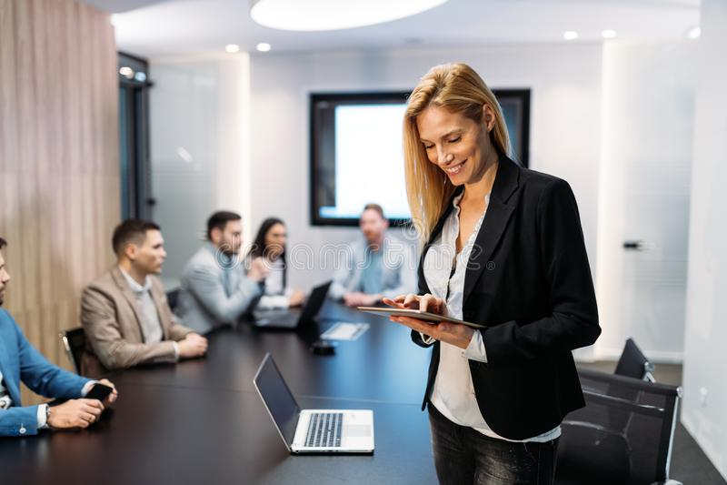 Empresaria atractiva que usa la tableta digital en oficina fotos de archivo