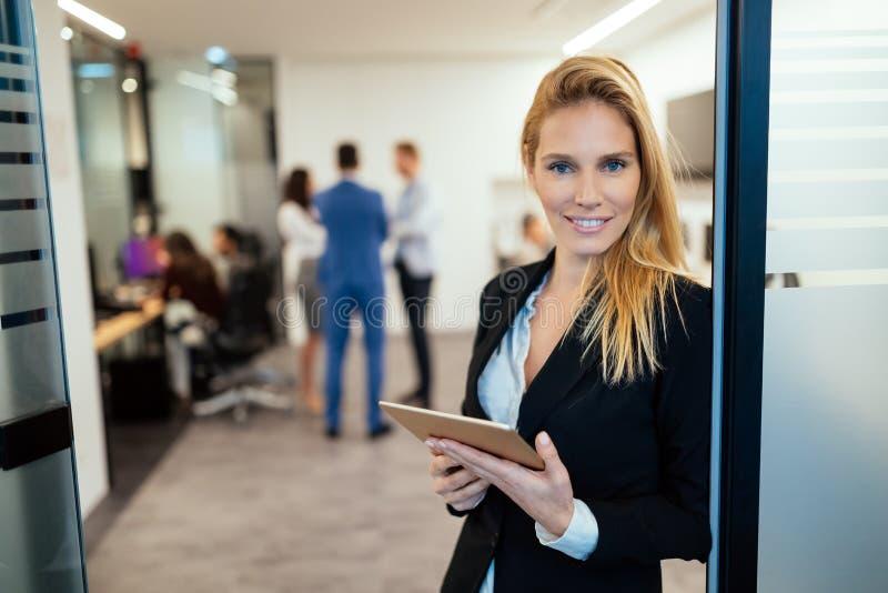 Empresaria atractiva que usa la tableta digital en oficina imagenes de archivo
