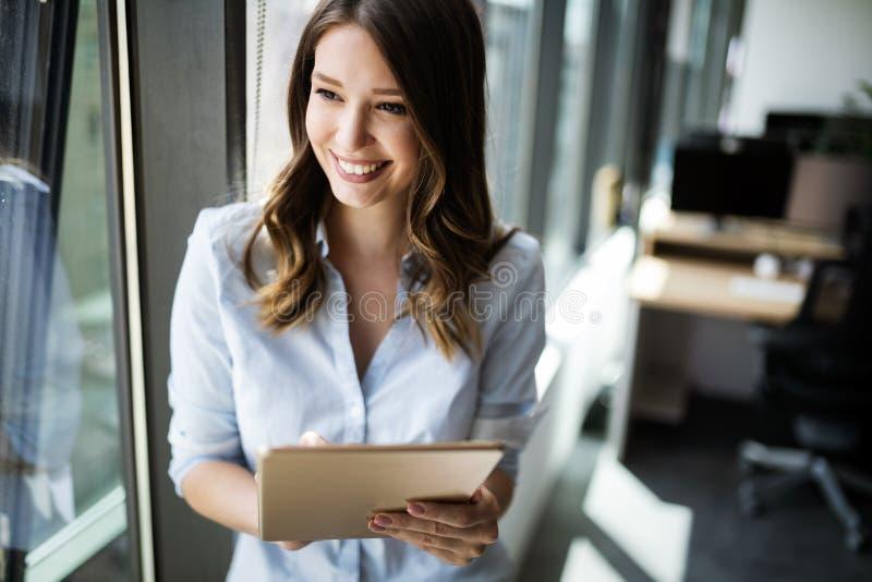 Empresaria atractiva que usa una tableta digital mientras que se coloca delante de ventanas foto de archivo libre de regalías