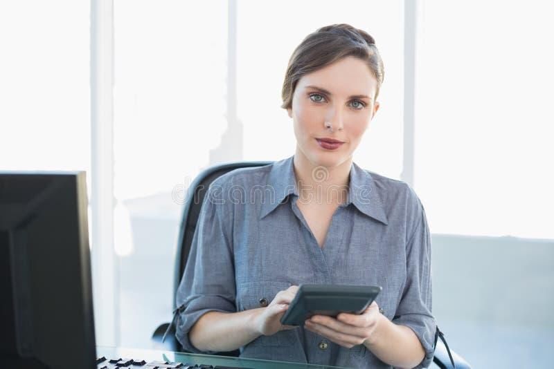 Empresaria atractiva seria que sostiene una calculadora que se sienta en su escritorio foto de archivo libre de regalías