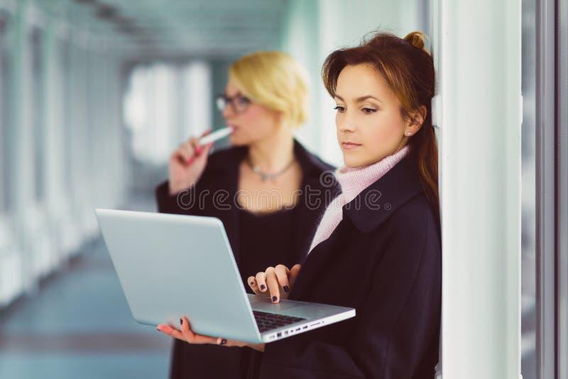 Empresaria atractiva sonriente dos que usa el ordenador portátil en el pasillo de la oficina foto de archivo