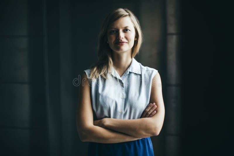 Empresaria auténtica rubia con la sonrisa cruzada de los brazos imagenes de archivo