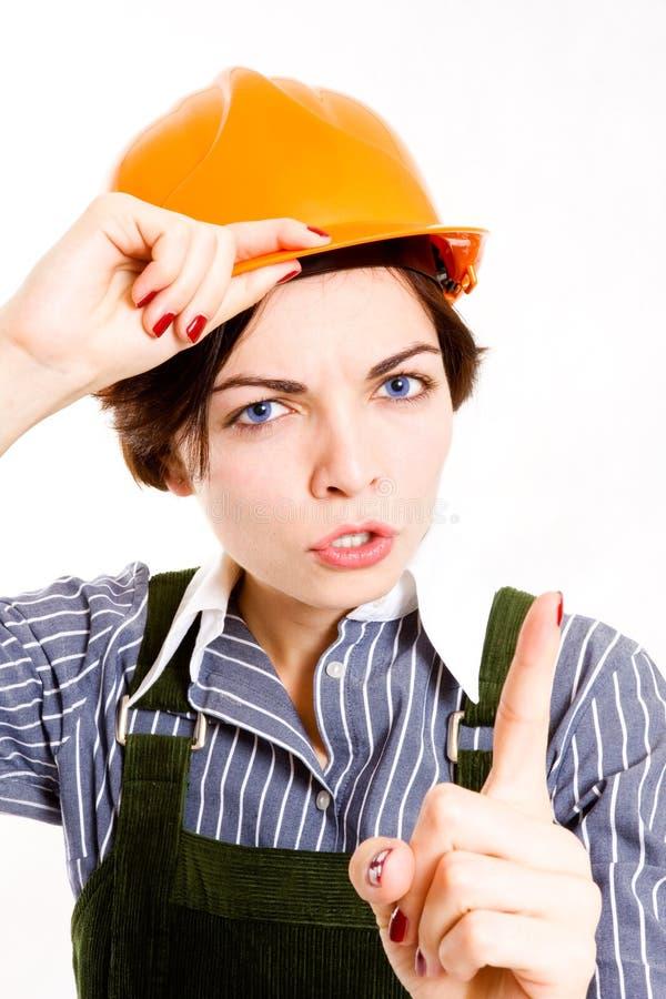 Empresaria bonita con señalar del casco. foto de archivo