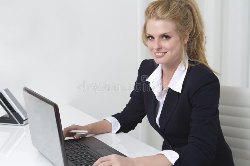 Empresaria bonita en el escritorio con la computadora portátil imagen de archivo libre de regalías