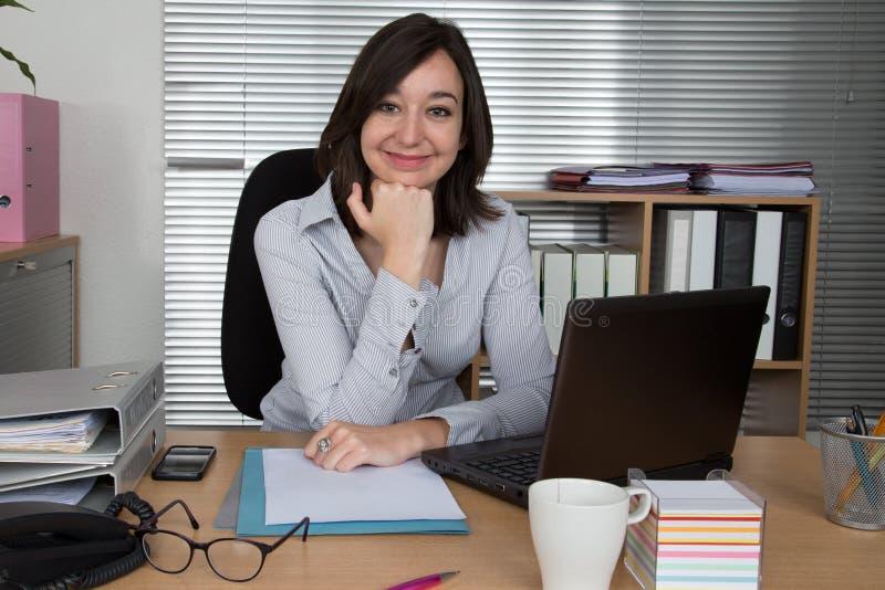 Empresaria bonita en la oficina con la mano a su barbilla fotografía de archivo