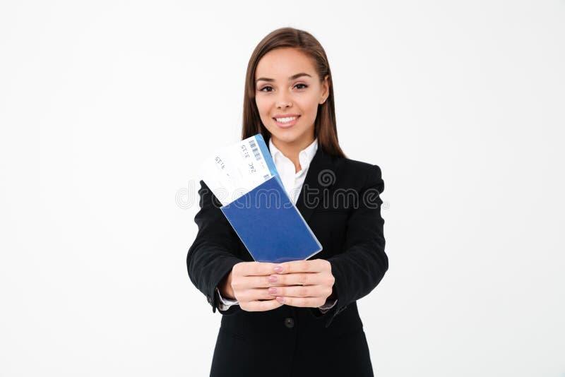 Empresaria bonita feliz que muestra boletos y el pasaporte imagen de archivo