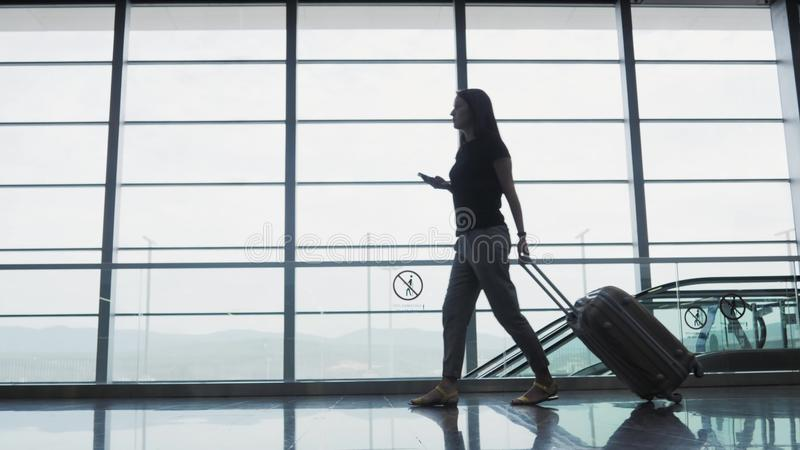 Empresaria bonita joven Using Smartphone en el aeropuerto mientras que espera su cola el registro, concepto que viaja fotos de archivo