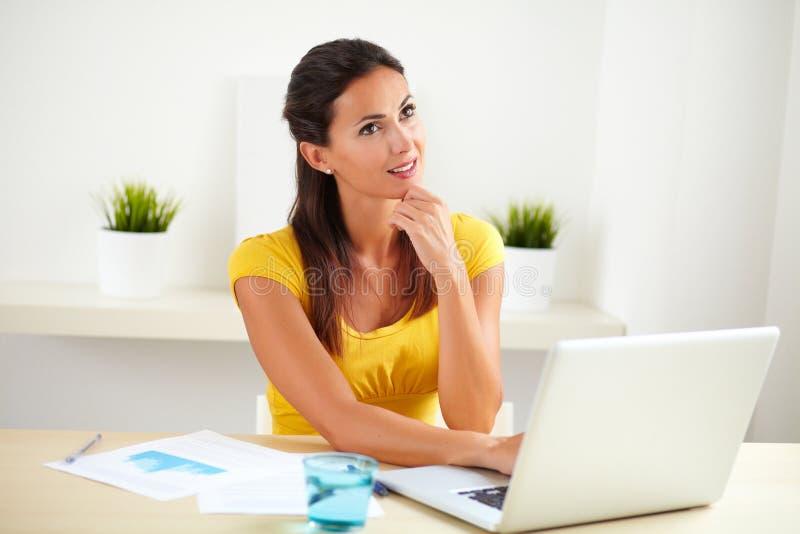 Empresaria bonita que se pregunta mientras que usa el ordenador portátil fotografía de archivo