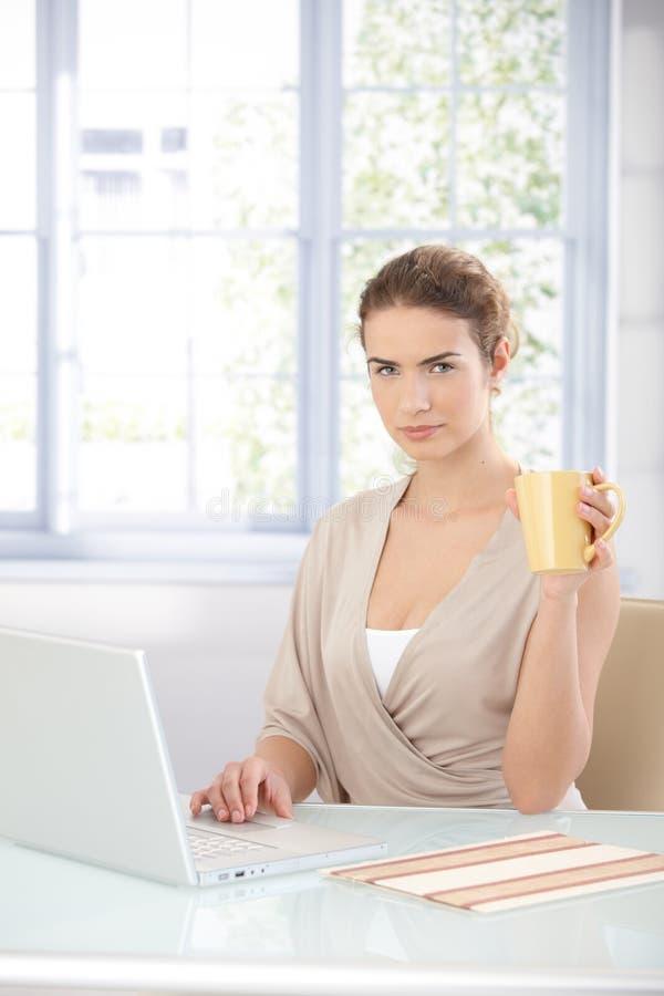 Empresaria bonita que trabaja en la computadora portátil imagen de archivo