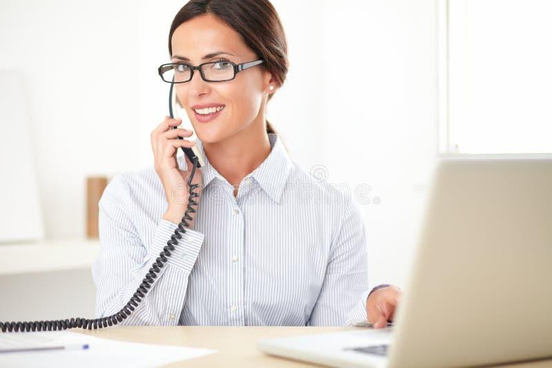 Empresaria bonita que usa el teléfono en la oficina foto de archivo libre de regalías