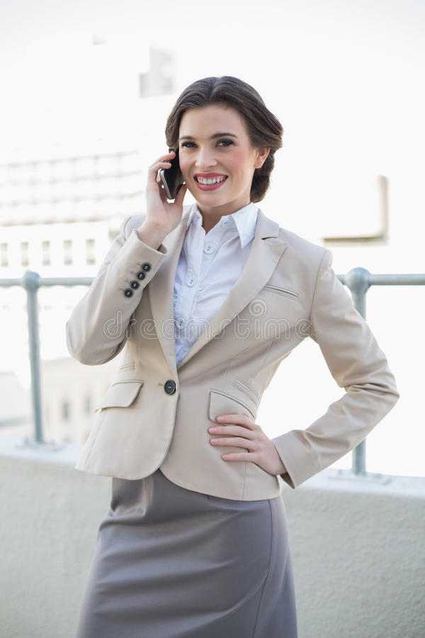 Empresaria cabelluda marrón elegante alegre que llama con su teléfono móvil foto de archivo