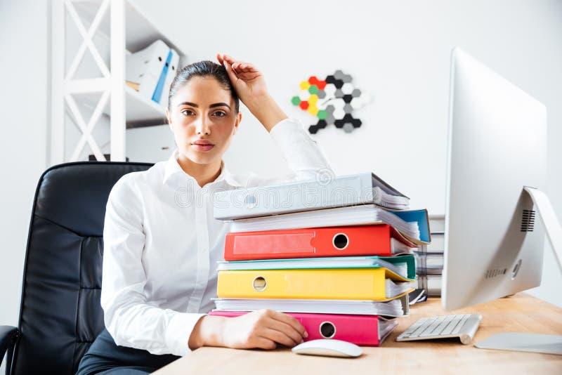 Empresaria cansada agotada que se sienta en el escritorio de oficina fotos de archivo libres de regalías