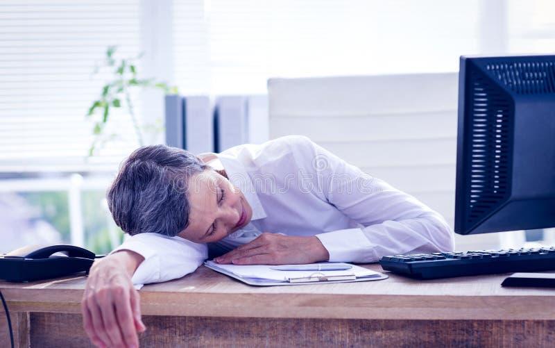 Empresaria cansada que duerme en su escritorio fotografía de archivo