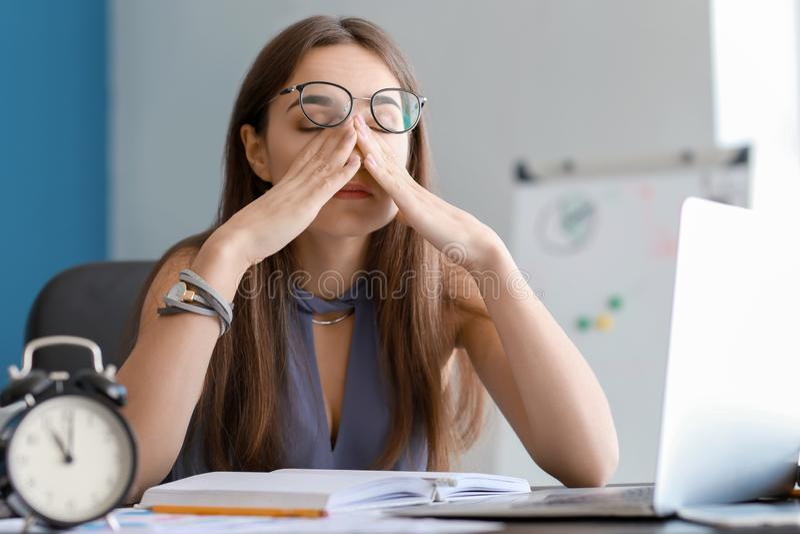 Empresaria cansada que intenta cumplir plazo en oficina imagenes de archivo