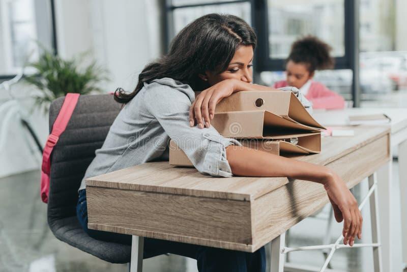 Empresaria cansada que miente en carpetas en el lugar de trabajo con la hija detrás fotos de archivo libres de regalías