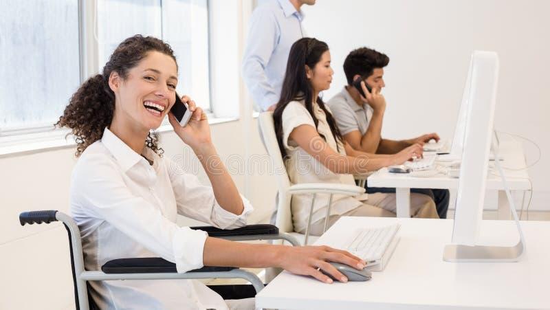 Empresaria casual en silla de ruedas en el teléfono que sonríe en la cámara imagenes de archivo