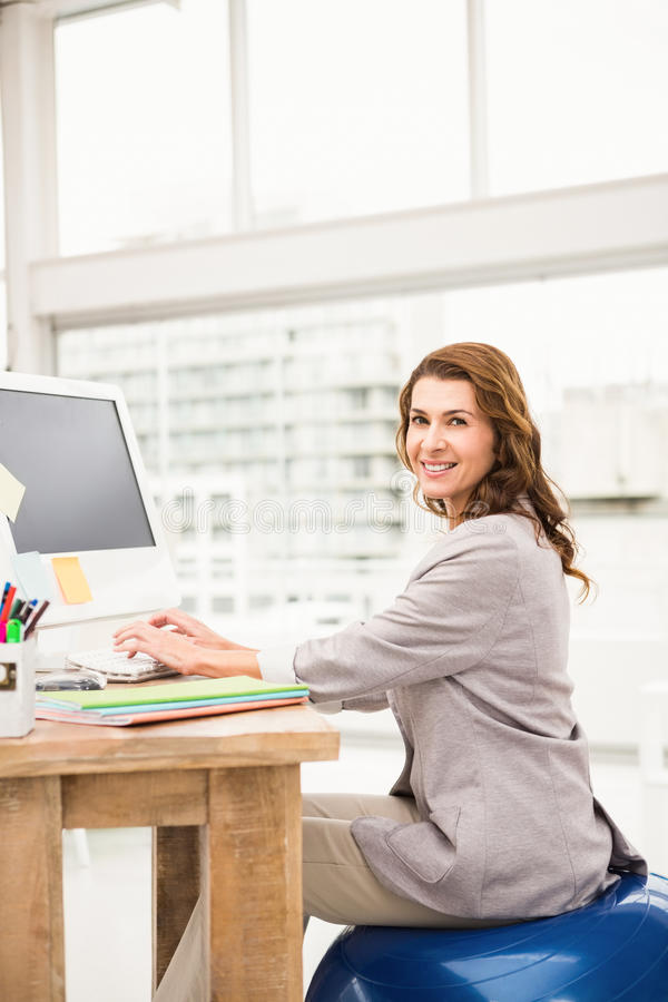 Empresaria casual que se sienta en bola del ejercicio mientras que trabaja foto de archivo