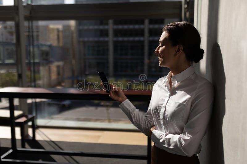 Empresaria caucásica joven que se inclina contra la pared y que usa el teléfono móvil en oficina fotos de archivo