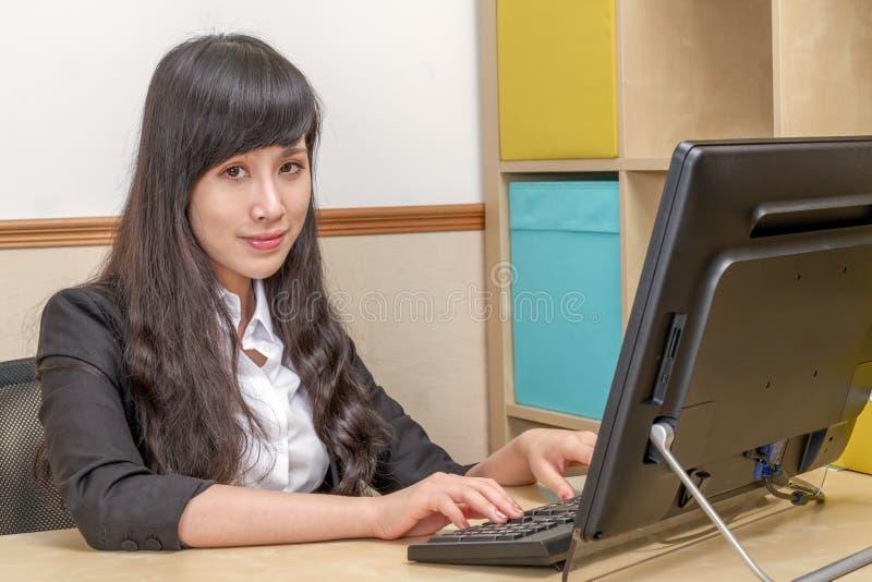 Empresaria china en mecanografiar del escritorio foto de archivo libre de regalías