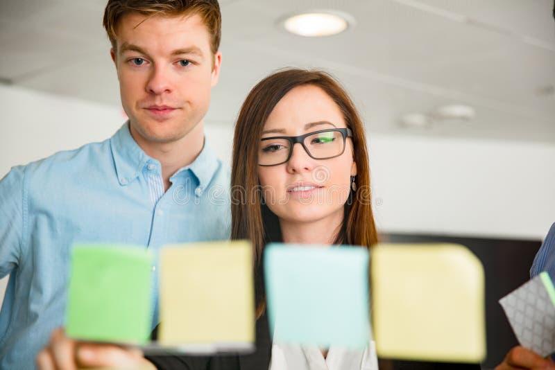 Empresaria And Colleague Looking en las notas pegadas en el vidrio imágenes de archivo libres de regalías