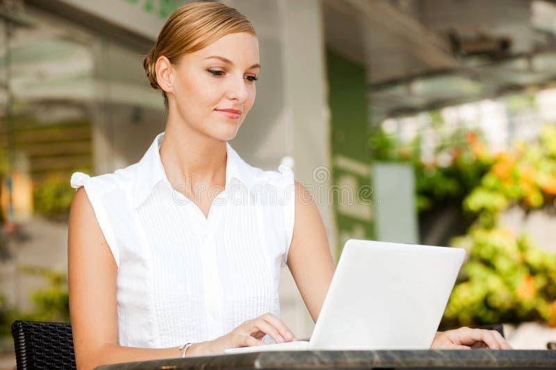 Empresaria con café y la computadora portátil fotos de archivo