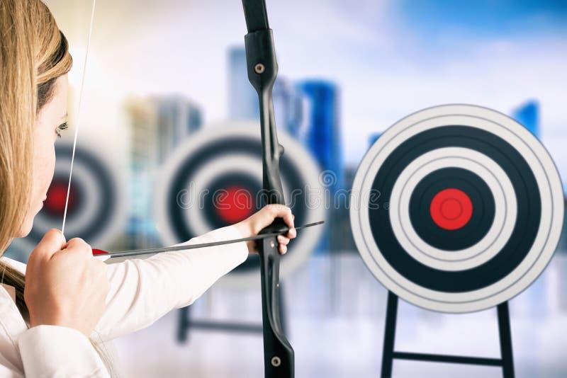 Empresaria con el arco y la flecha que se?ala el centro de la blanco fotografía de archivo libre de regalías