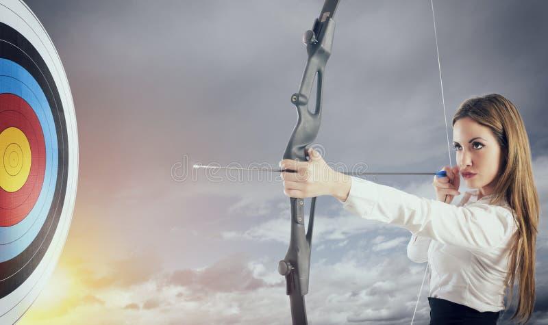 Empresaria con el arco y la flecha que se?ala el centro de la blanco imagen de archivo libre de regalías