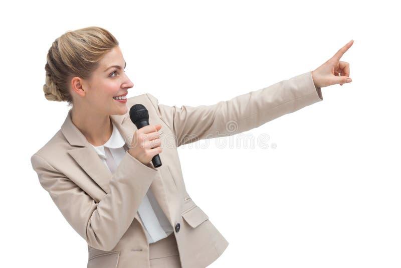 Empresaria con el micrófono que indica algo imágenes de archivo libres de regalías