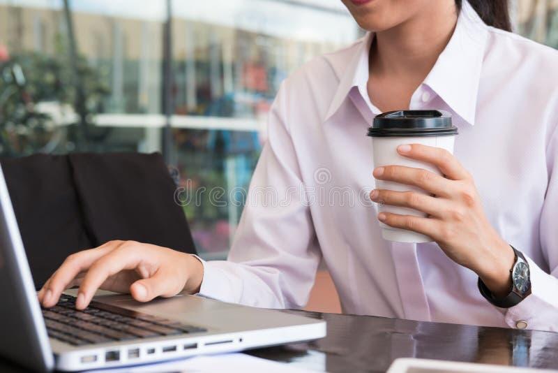 Empresaria con el ordenador portátil que se sienta fuera de buildi de la oficina imágenes de archivo libres de regalías
