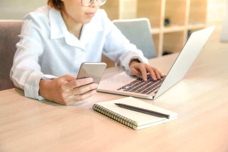 Empresaria con el ordenador portátil y el smartphone fotografía de archivo libre de regalías