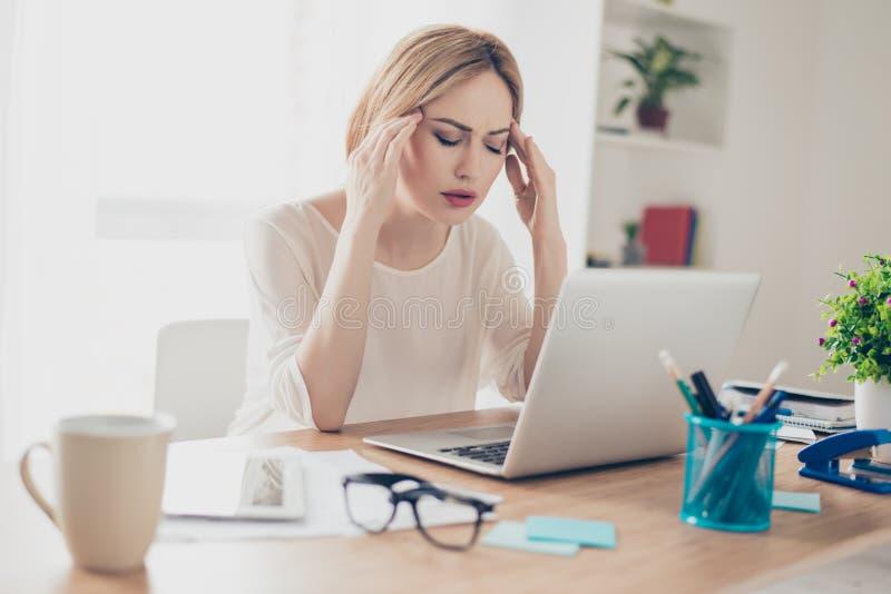 Empresaria con exceso de trabajo que sufre de dolor de cabeza y que piensa ho fotografía de archivo libre de regalías